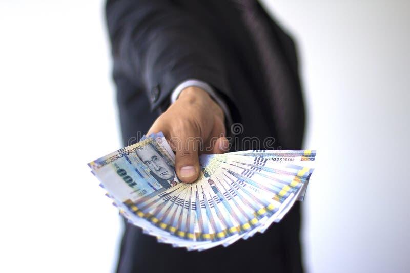 Gesch?ftsmann, der 100 Sohlenrechnungen in einem Fan, peruanisches W?hrungskonzept h?lt stockbild