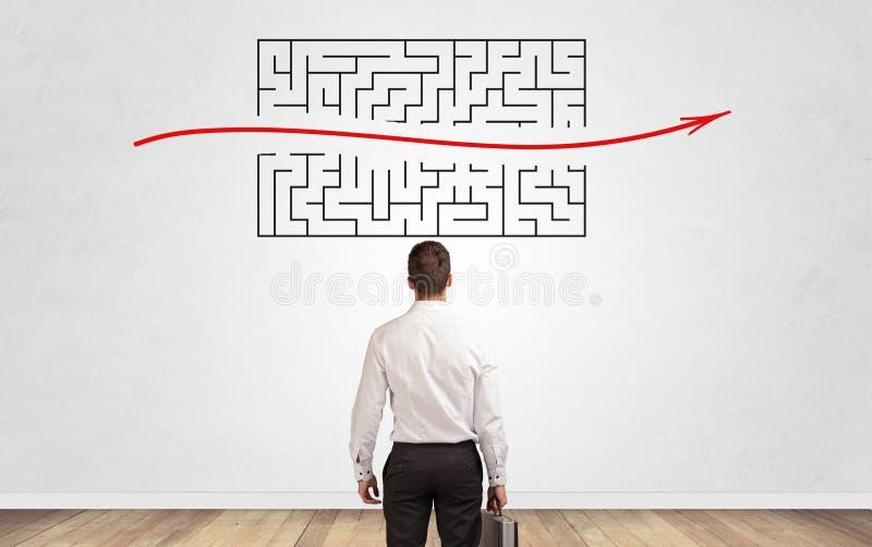 Gesch?ftsmann, der zu einem Labyrinth auf einer Wand schaut lizenzfreies stockbild