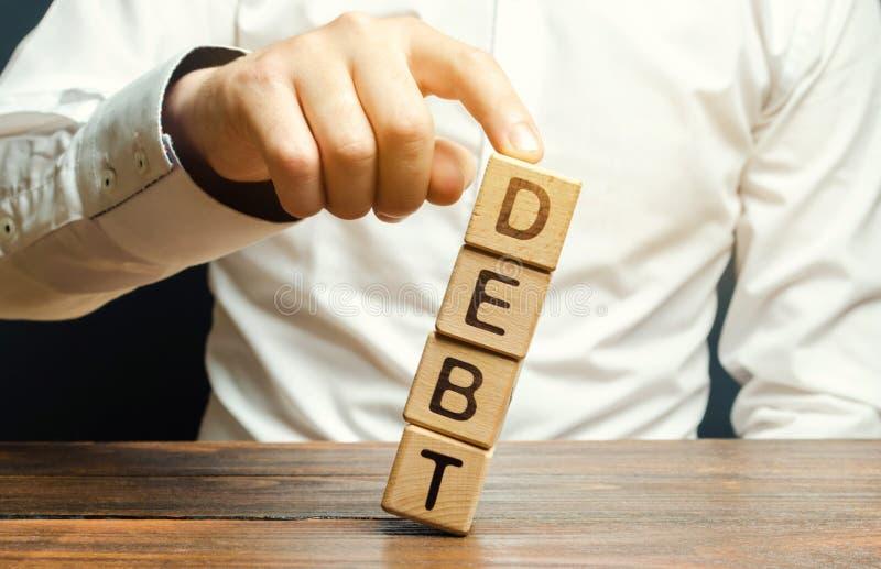 Gesch?ftsmann entfernt Holzkl?tze mit der Wort Schuld Konzessionen an Schuldner oder Annullierung ist das teilweise oder Gesamtve stockbild