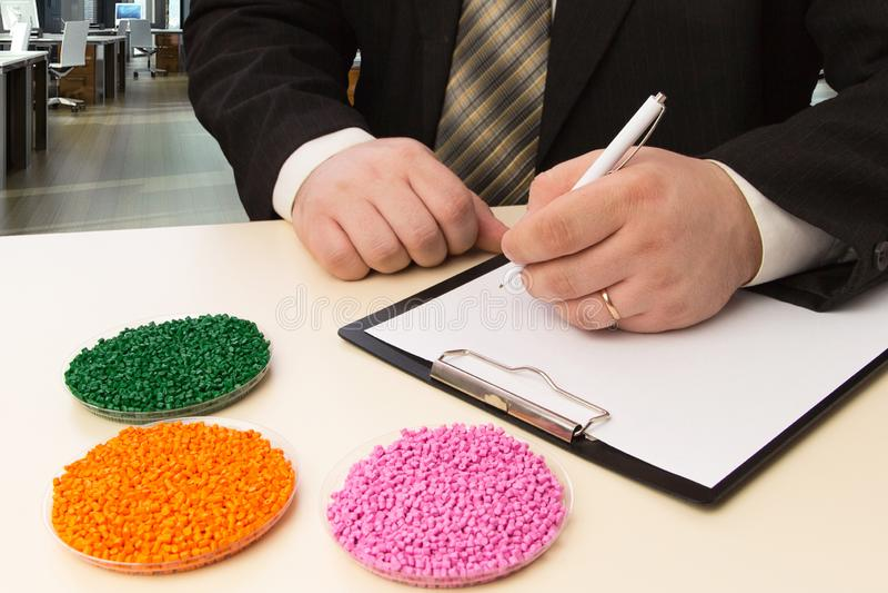 Gesch?ftsmann im B?ro unterzeichnet einen Vertrag f?r die Versorgung von Plastikk?rnchen f?r Industrie Plastikrohstoff in den K?r lizenzfreie stockbilder