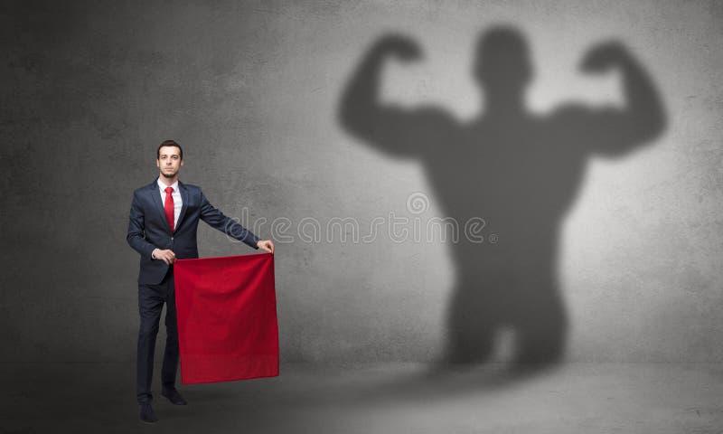 Gesch?ftsmann mit starkem Heldschatten- und -Stierk?mpferkonzept stockfotografie