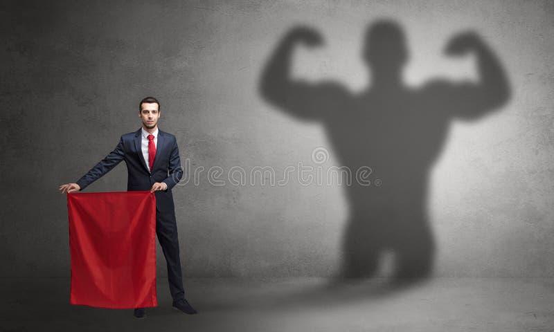 Gesch?ftsmann mit starkem Heldschatten- und -Stierk?mpferkonzept lizenzfreie stockbilder