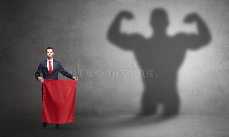 Gesch?ftsmann mit starkem Heldschatten- und -Stierk?mpferkonzept lizenzfreies stockfoto