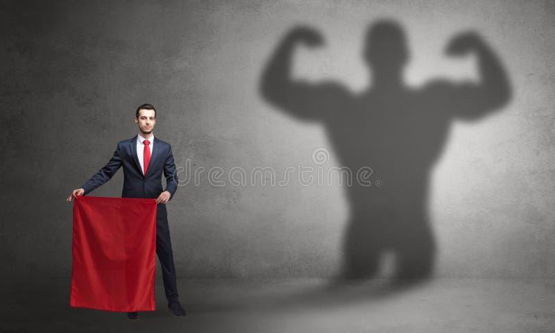 Gesch?ftsmann mit starkem Heldschatten- und -Stierk?mpferkonzept lizenzfreie stockfotos