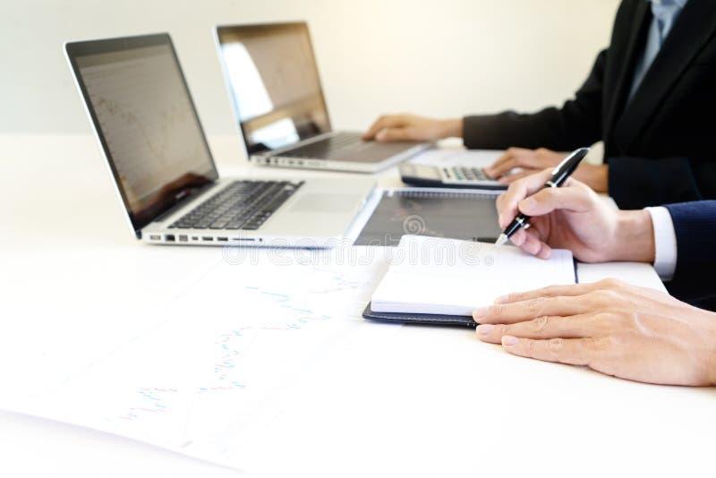 Gesch?ftsmann und Frau sitzen an ther Tisch, der Computerlaptop betrachtet lizenzfreie stockfotos