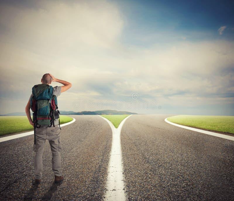 Gesch?ftsmann vor einem Crossway muss den richtigen Weg vorw?hlen stockfotografie