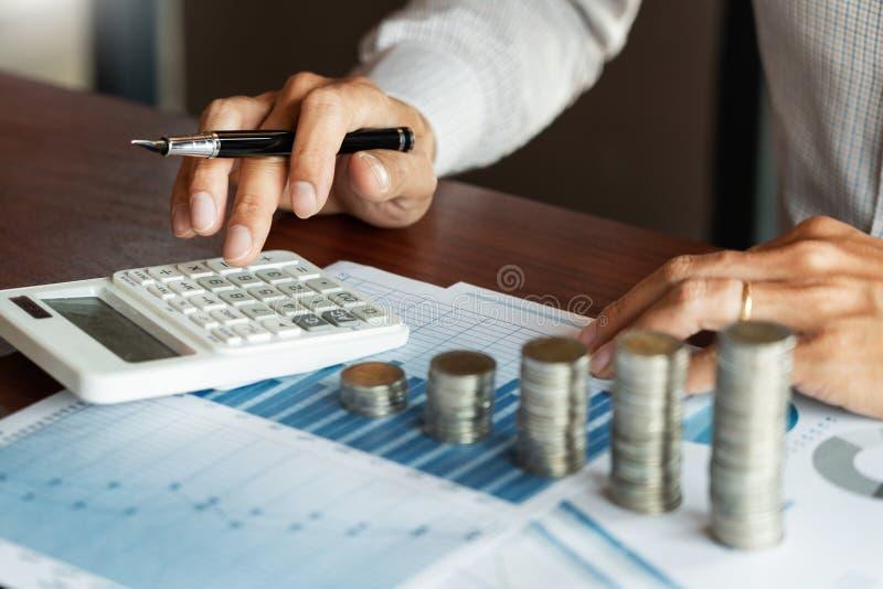 Gesch?ftsmannbuchhalter Calculating auf Datendokumenten und Stapel Stapel M?nzen, die Einsparungensgeldanlage Finanzbudget lizenzfreies stockbild