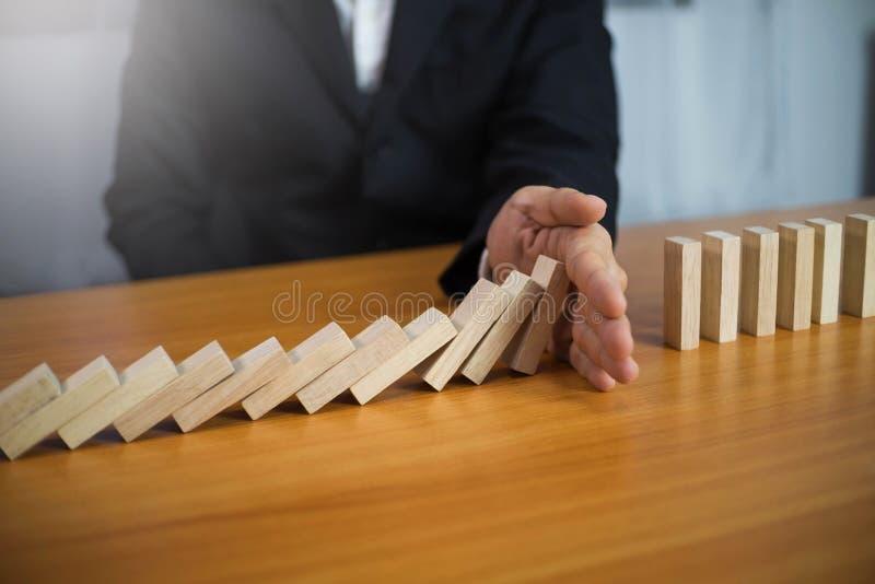 Gesch?ftsmannhand stoppt ununterbrochene umgeworfene Bedeutung des Dominos, die Unternehmenszusammenbruch hinderte Halt ?ber dies lizenzfreie stockfotografie