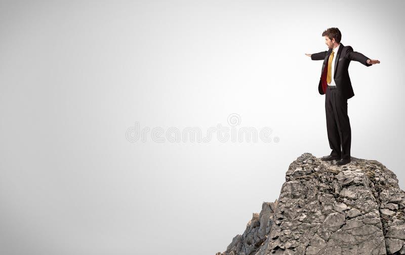 Gesch?ftsperson auf die Oberseite des Felsens mit Kopienraum lizenzfreie stockfotos