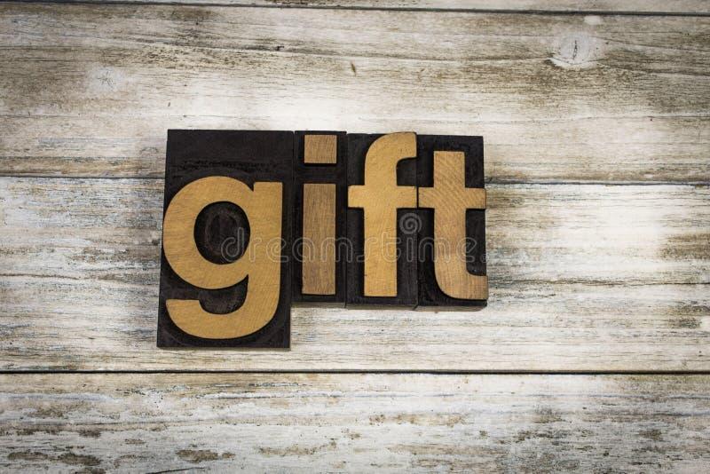 Geschenk-Briefbeschwerer-Wort auf hölzernem Hintergrund stockfotografie