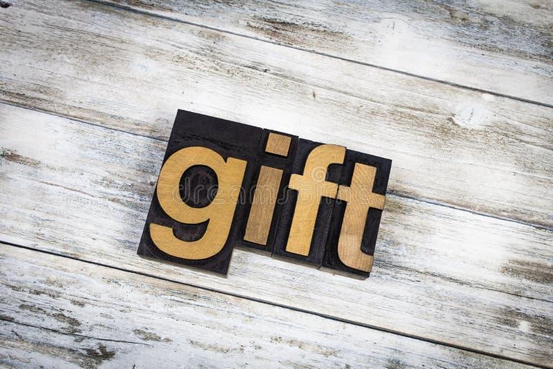 Geschenk-Briefbeschwerer-Wort auf hölzernem Hintergrund lizenzfreie stockbilder