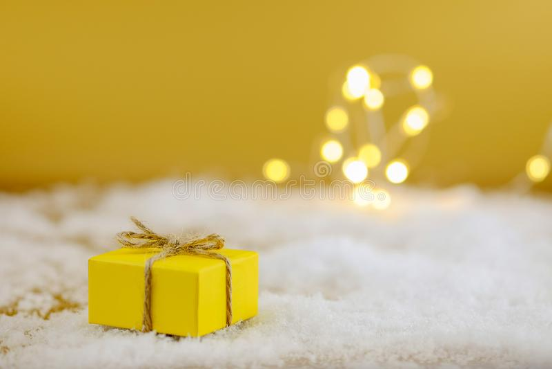 Geschenk im gelben Packpapier auf einem Goldhintergrund lizenzfreies stockfoto
