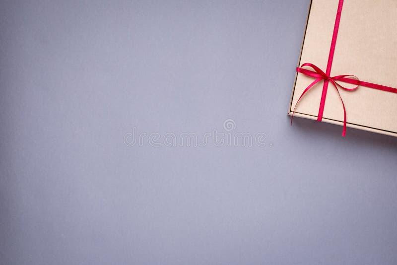 Geschenk im Kasten mit Burgunder-Satinband auf einem grauen Hintergrund lizenzfreies stockbild