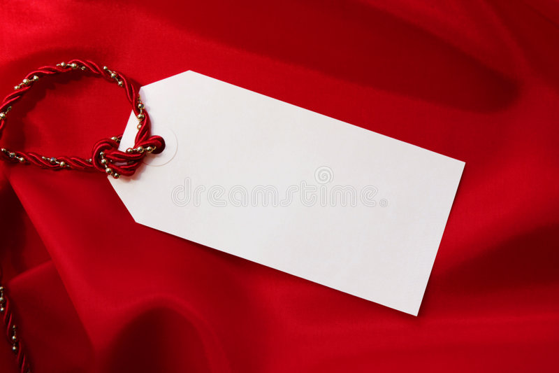 Geschenk-Marke auf rotem Satin lizenzfreie stockbilder