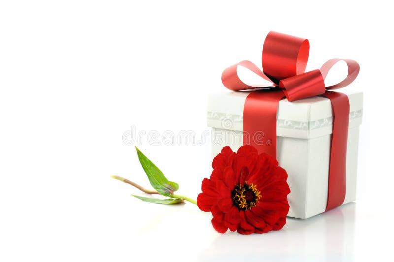 Geschenk mit rotem Farbband und Blume stockbild
