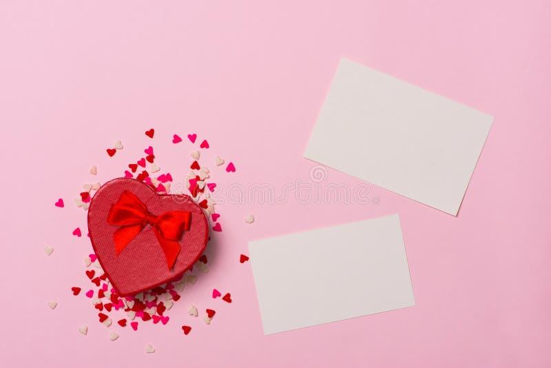 Geschenk oder Geschenkbox, Papierherz und Konfettis auf Draufsicht des Rosahintergrundes Über weißem Hintergrund flache Lageart stockfotos
