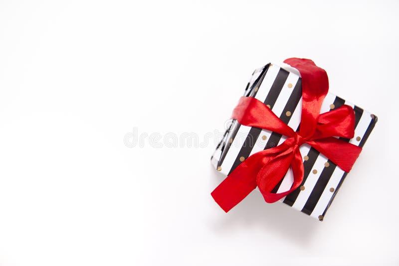 Geschenk- oder Geschenkkarton in weißen und schwarzen Streifen mit rotem Bandbogen isoliert auf der weißen Tischübersicht Mindest lizenzfreie stockfotos