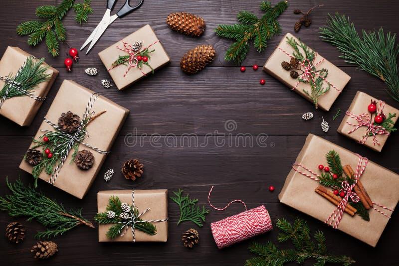 Geschenk oder Präsentkarton eingewickelt im Kraftpapier mit Weihnachtsdekoration auf rustikalem hölzernem Hintergrund von oben fl lizenzfreie stockbilder