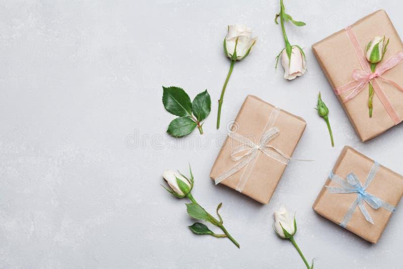 Geschenk oder Präsentkarton eingewickelt im Kraftpapier und in der rosafarbenen Blume auf grauer Tabelle von oben Flaches Lageanr lizenzfreies stockbild