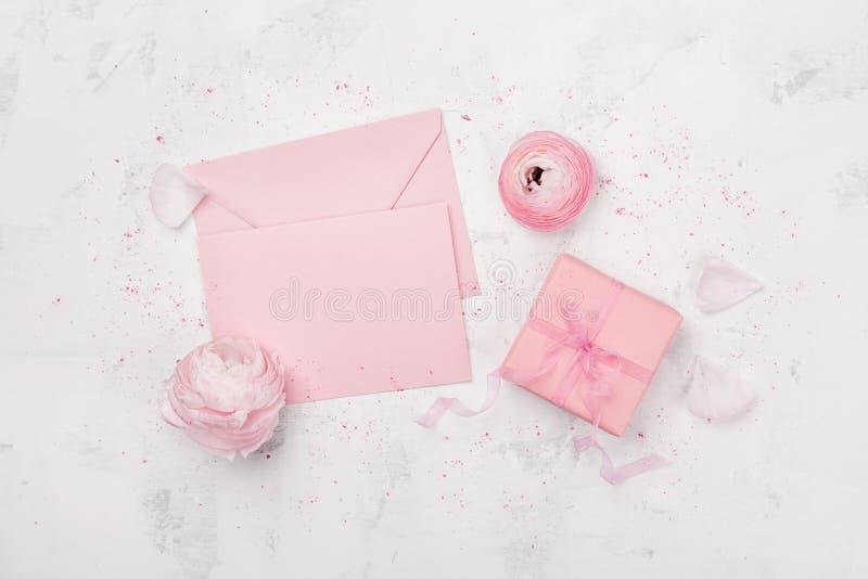 Geschenk oder Präsentkarton, rosa Papierfreier raum und Ranunculus blühen auf weißer Tabelle von oben genanntem für Heiratsmodell stockfoto