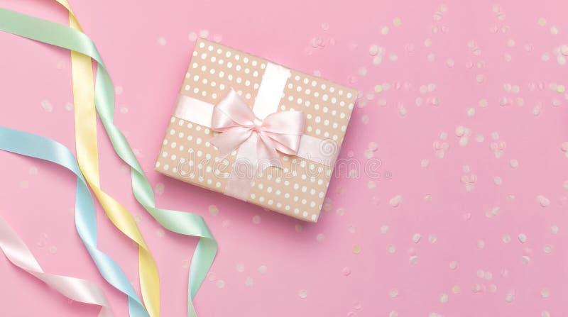 Geschenk oder Präsentkarton, schönes festliches Band, Konfetti auf Draufsicht des Rosahintergrundes Flache gelegte Zusammensetzun stockbild