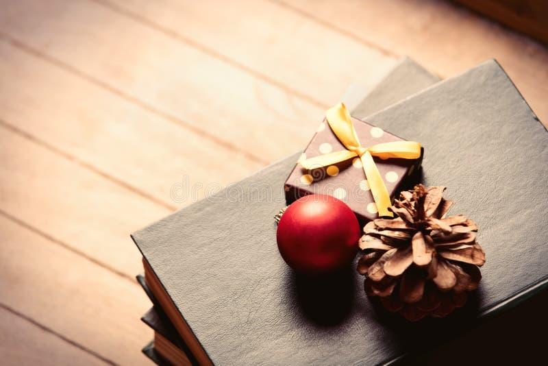 Geschenk, Tannenzapfen, Flitter und Bücher stockfoto