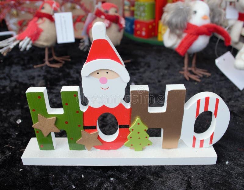 Geschenk Weihnachtenhölzernes HoHo Weihnachtsmann verziert mit Sternen und stockbilder
