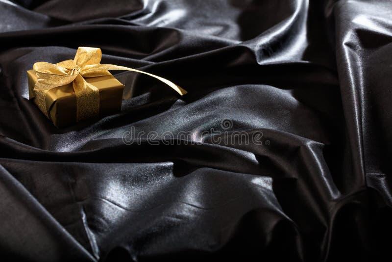 Geschenkbox auf einem schwarzen Satinhintergrund stockbilder