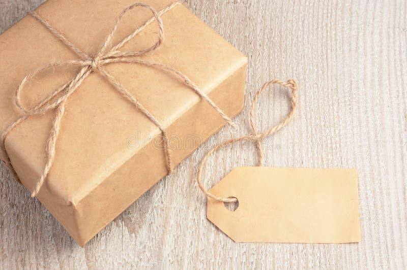 Geschenkbox in das braune Papier gebunden durch Schnur und leeres Tag auf weißem Holztisch mit Raum für Text stockfotos