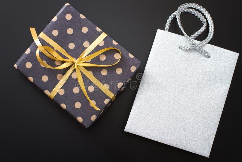 Geschenkbox in den Tupfen und Papiertüte auf schwarzem Hintergrund Draufsicht- und Kopienraum lizenzfreies stockfoto