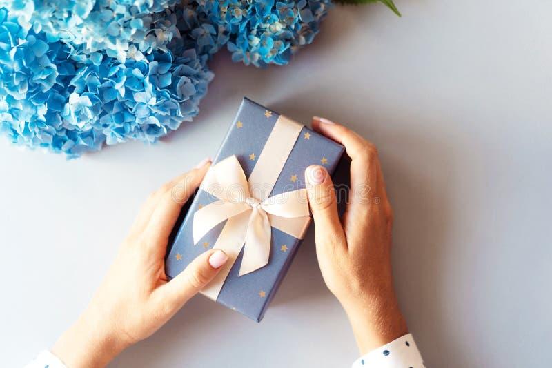Geschenkbox in der Hand und Blumen auf Hintergrund stockfoto