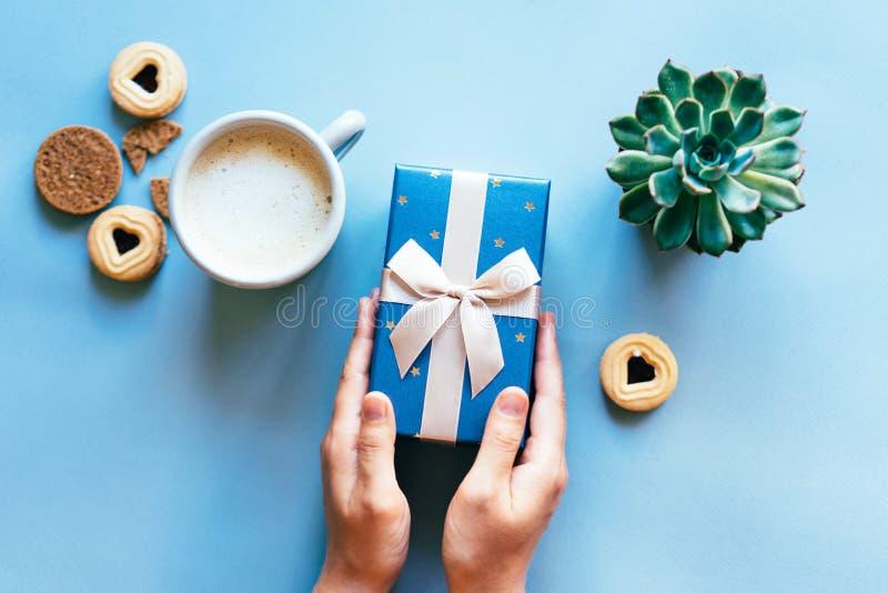 Geschenkbox, die Hände der Frauen, Kaffee lizenzfreie stockfotos