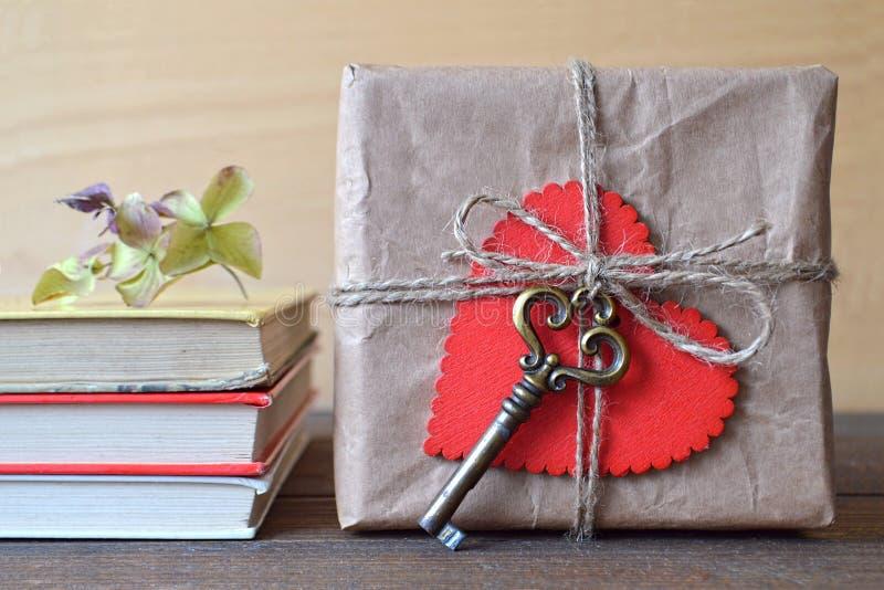 Geschenkbox eingewickelt im braunen Papier, verziert mit Herzen und altem Schlüssel stockbild