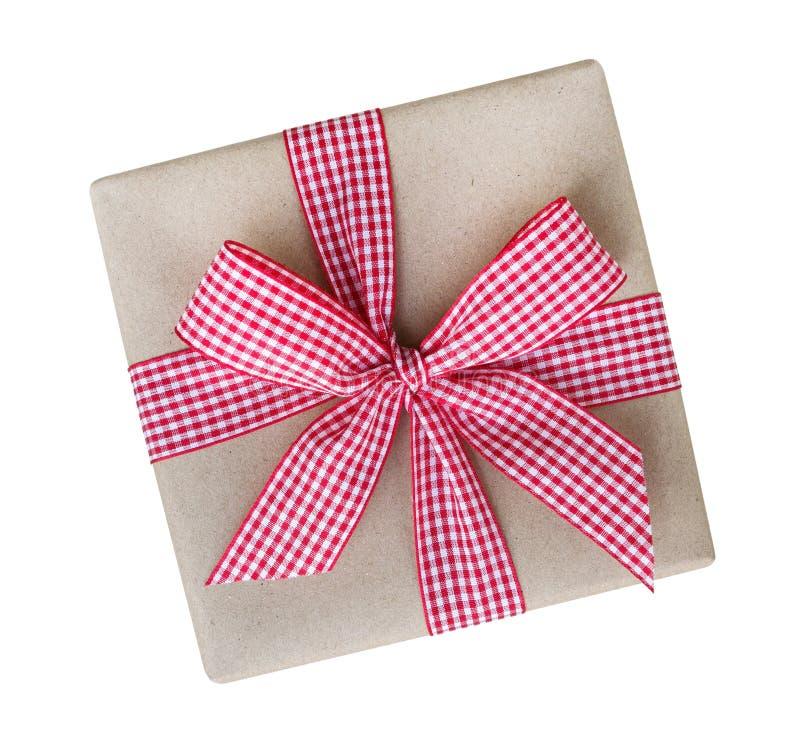 Geschenkbox eingewickelt im braunen Recyclingpapier mit Draufsicht des roten und weißen Ginghambandbogens lokalisiert auf weißem  stockfotos