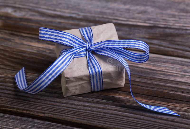 Geschenkbox eingewickelt im natürlichen Papier mit blauem Band stockbilder