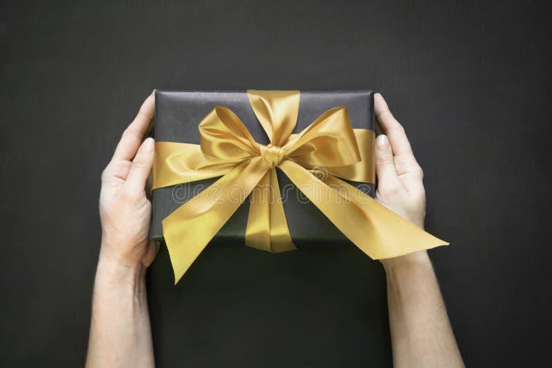 Geschenkbox eingewickelt im schwarzen Papier mit Goldband in der weiblichen Hand auf schwarzer Oberfläche Beschneidungspfad einge stockfoto