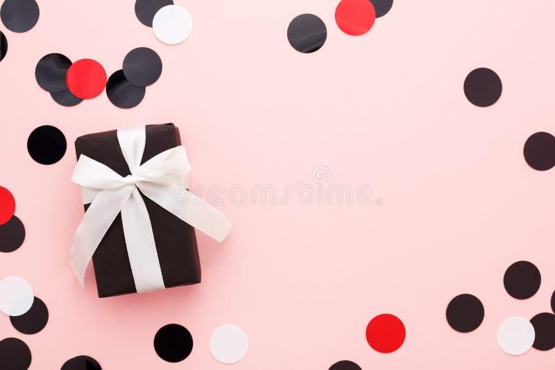 Geschenkbox eingewickelt im schwarzen Papier- u. Weißbogen auf rosa Hintergrund w lizenzfreie stockfotografie