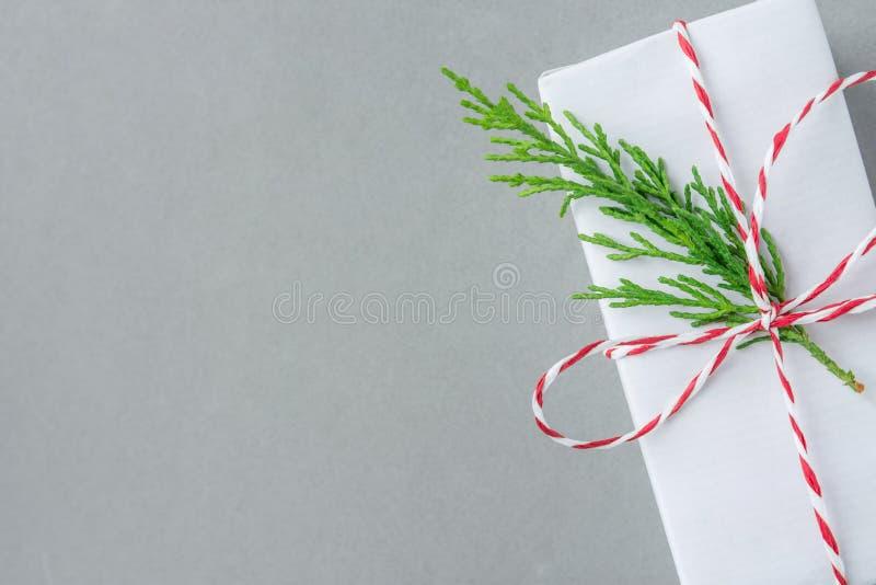 Geschenkbox eingewickelt im Weißbuch gebunden mit dem gestreiften roten Bandgrün-Wacholderbuschzweig auf grauem Hintergrund Gesch stockbild