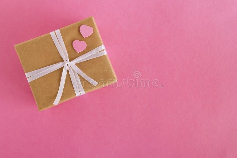 Geschenkbox eingewickelt vom Kraftpapier- und Weißband mit zwei rosa Herzen auf dem rosa Hintergrund lizenzfreie stockfotos