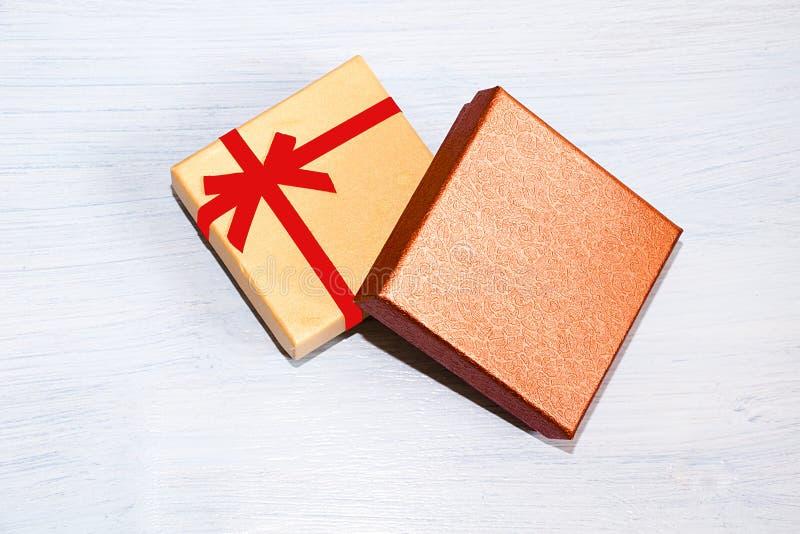 Geschenkbox für die verpackenden Geschenke, die auf blauem Hintergrund liegen stockbild