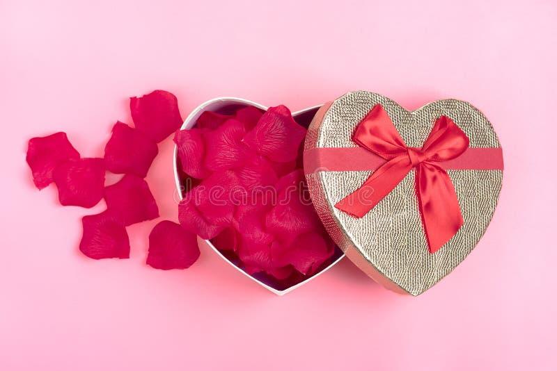 Geschenkbox in Form eines Herzens mit den rosafarbenen Blumenblättern nach innen auf einem Rosahintergrund glücklichen Valentinst stockbild