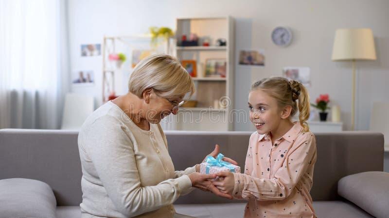 Geschenkbox gebende der Gro?mutter und umarmende Enkelin, Feiertags?berraschung lizenzfreie stockbilder