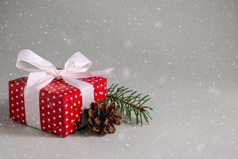 Geschenkbox im roten Packpapier mit weißem Bogen- und Kiefernkegel unter Schnee lizenzfreie stockbilder