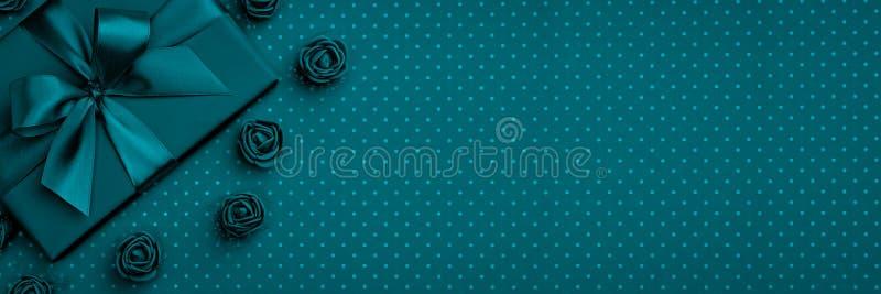 Geschenkbox mit Bogen und Band, Blume stieg Draufsicht über dunkelblauen oder Türkishintergrund Flache Lage Beschneidungspfad ein stockbild