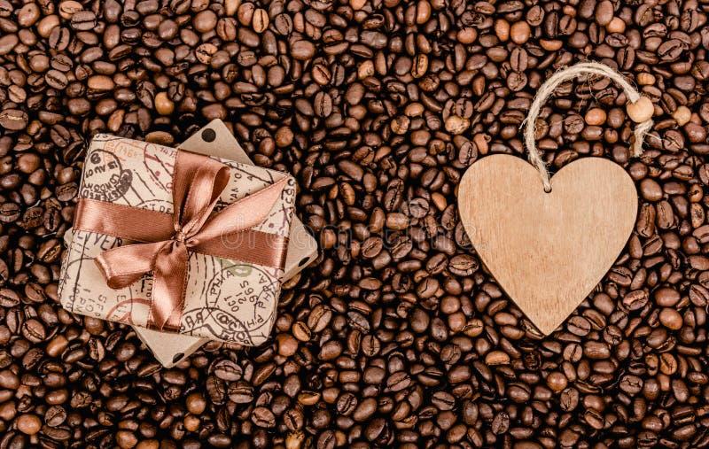 Geschenkbox mit Bogen und Valentinsgruß Geschenkbox mit Band und hölzernem Herzen Kaffeehintergrund und -geschenk lizenzfreies stockbild