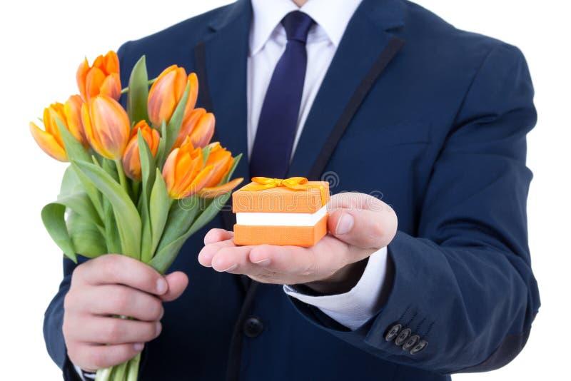 Geschenkbox mit Ehering und Blumen in den männlichen Händen an lokalisiert stockfotos