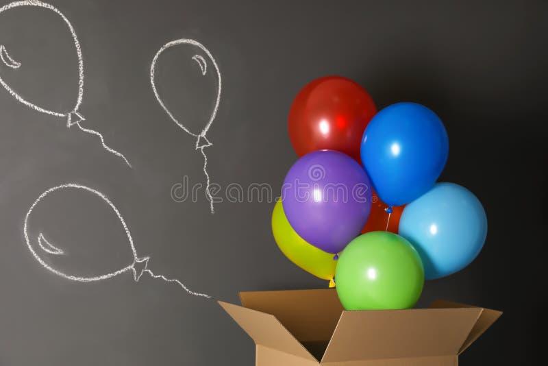 Geschenkbox mit hellen Luftballonen und Kreidezeichnung lizenzfreie stockbilder