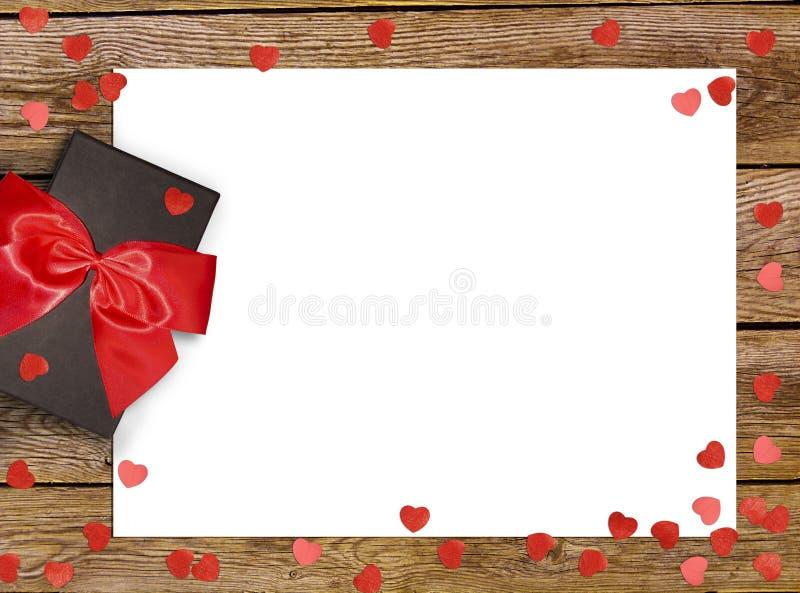 Geschenkbox mit rotem Bogenband und Papierherz auf hölzernem Hintergrund für Valentinsgrußtag lizenzfreie stockfotos