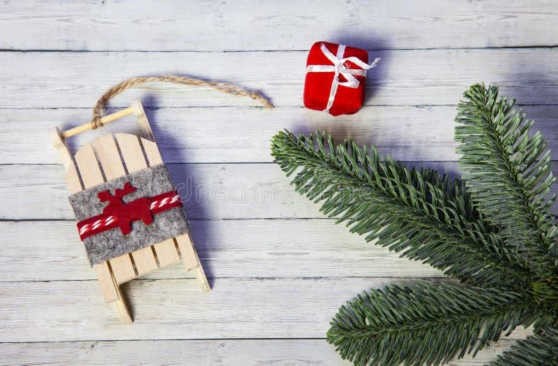 Geschenkbox-, Sankt-Pferdeschlitten und Tannenzweige auf einem hölzernen Hintergrund, Draufsicht lizenzfreie stockbilder