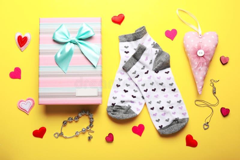 Geschenkbox, Socken und anderes Zubehör auf gelbem Hintergrund stockfoto